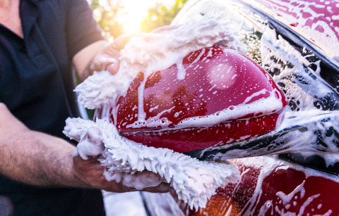 Man worker washing side mirror of a red car with sponge on a car wash.- Stock Photo or Stock Video of rcfotostock | RC-Photo-Stock