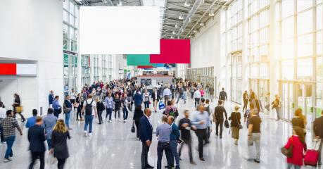 Many anonymous people are walking around advertising banner at a trade fair, copyspace for your individual text.- Stock Photo or Stock Video of rcfotostock   RC-Photo-Stock