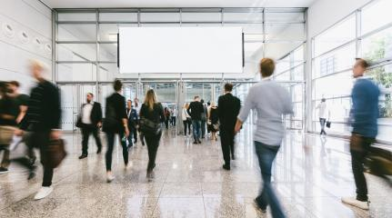 Many trade fair visitors run under advertising poster - Stock Photo or Stock Video of rcfotostock   RC-Photo-Stock