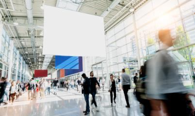 Many trade fair visitors walk under a blank billboard through a hall : Stock Photo or Stock Video Download rcfotostock photos, images and assets rcfotostock | RC-Photo-Stock.:
