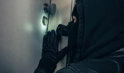 Masked burglar with flashlight breaking into a house door at night- Stock Photo or Stock Video of rcfotostock | RC-Photo-Stock