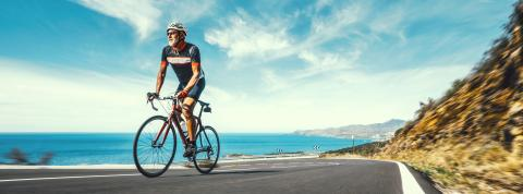 Mature Adult on a racing bike climbing the hill at mediterranean sea landscape coastal road- Stock Photo or Stock Video of rcfotostock | RC-Photo-Stock