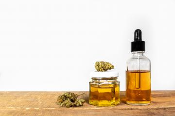 Medicine cannabis buds and hemp oil in glass bottle on wooden table with white background - alternative CBD medicine