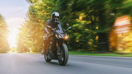 motorcycle riding on the forest road at summer. driving on the empty road on a motorbike trip. copyspace for your individual text.- Stock Photo or Stock Video of rcfotostock | RC-Photo-Stock