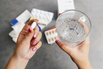 one round white pill in young female hand and Glass of Water for medication. Health care and medical concept.- Stock Photo or Stock Video of rcfotostock | RC-Photo-Stock