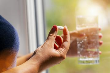 one round white pill in young female hand. Woman takes medicines with glass of water. Daily norm of vitamins, effective drugs, pharmacy and mental health concept image- Stock Photo or Stock Video of rcfotostock | RC-Photo-Stock