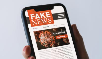 Online Corona Fake news on a mobile phone. Close up of woman reading Fake news or articles about covid-19 in a smartphone screen application. Hand holding smart device. Mockup. COVID19 nCov Outbreak.- Stock Photo or Stock Video of rcfotostock | RC-Photo-Stock