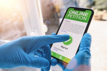 Online Petition on a mobile phone. Close up of caregiver signed Online Petition in a smartphone screen application. Hand holding smart device. Mockup website at Covid-19 coronavirus epidemic - Stock Photo or Stock Video of rcfotostock | RC-Photo-Stock