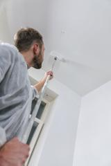 painter working with paint roller to paint the ceiling of a room with white color. do it yourself concept image- Stock Photo or Stock Video of rcfotostock | RC-Photo-Stock