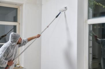 painter working with paint roller to paint the wall of a room. do it yourself concept image - Stock Photo or Stock Video of rcfotostock | RC-Photo-Stock