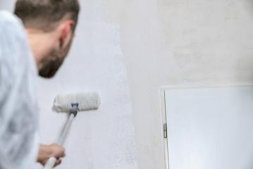 painter working with paint roller to paint the wall of a room with white color. do it yourself concept image- Stock Photo or Stock Video of rcfotostock | RC-Photo-Stock