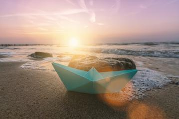 paper boat sailing on at the beach at a romantic sunset : Stock Photo or Stock Video Download rcfotostock photos, images and assets rcfotostock | RC-Photo-Stock.:
