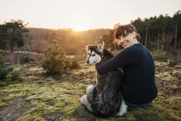 Person and dog are having fun and looking at the camera. The woman and the husky enjoy the view in a beautiful landscape. Hugging at sunset.  : Stock Photo or Stock Video Download rcfotostock photos, images and assets rcfotostock | RC-Photo-Stock.: