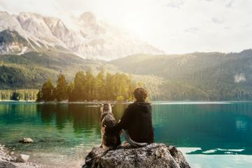 person with a dog in the mountains at a beautiful lake at sunset. Traveling with a pet. Happy satisfied time together. Friendship between man woman and dog. hugs.  : Stock Photo or Stock Video Download rcfotostock photos, images and assets rcfotostock | RC-Photo-Stock.: