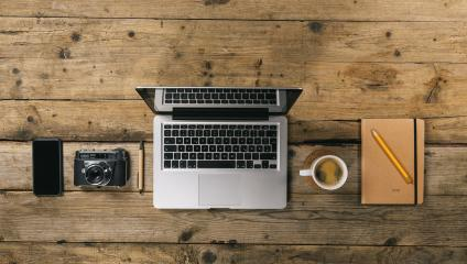 Photographer office desk with laptop, silver notebook, mobile phone, pen, camera and coffee cup, flat lay. Top view with copyspace for your individual text.- Stock Photo or Stock Video of rcfotostock | RC-Photo-Stock
