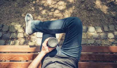 Point of view shot of a man sits on a bench in the park and holding a take away coffee- Stock Photo or Stock Video of rcfotostock | RC-Photo-Stock