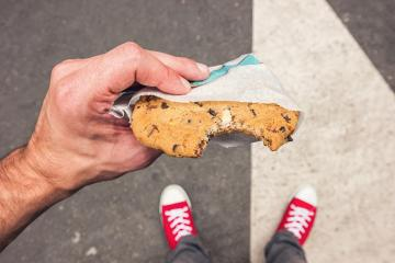 Point of view shot of a man standing along at the street and eats a cookie- Stock Photo or Stock Video of rcfotostock | RC-Photo-Stock