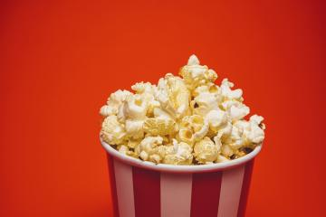 Popcorn in a round box and around on a bright red background.- Stock Photo or Stock Video of rcfotostock | RC-Photo-Stock