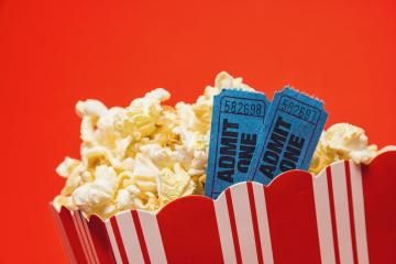 popcorn in striped box with two tickets to the cinema on red background- Stock Photo or Stock Video of rcfotostock | RC-Photo-Stock