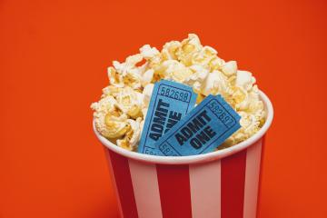 Popcorn with cinema movie in a round box and around on a bright red background.- Stock Photo or Stock Video of rcfotostock | RC-Photo-Stock