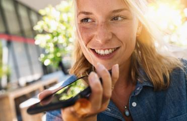 Portrait of a girl using the voice recognition of the phone sitting in a trendy cosy coffee shop cafe- Stock Photo or Stock Video of rcfotostock | RC-Photo-Stock