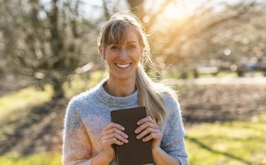 Portrait of a happy female student holding books and looking at camera outdoors : Stock Photo or Stock Video Download rcfotostock photos, images and assets rcfotostock | RC-Photo-Stock.: