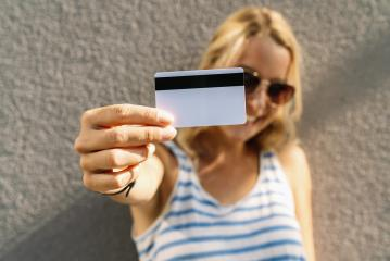 Portrait of a pretty young woman dressed in sweater holding credit card at her face. copyspace for your individual text. - Stock Photo or Stock Video of rcfotostock | RC-Photo-Stock