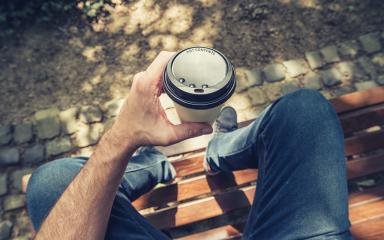 POV image of man sits on a bench and holding paper cup of coffee at a summer day in the park : Stock Photo or Stock Video Download rcfotostock photos, images and assets rcfotostock | RC-Photo-Stock.: