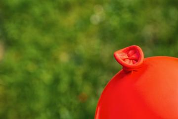 Red ballon knot against green background, copyspace for your individual text.- Stock Photo or Stock Video of rcfotostock | RC-Photo-Stock