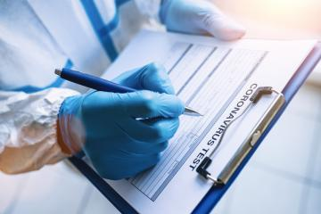 Researcher fills out a coronavirus test data sheet with pen in protective clothing in a clinic at Covid-19 coronavirus epidemic- Stock Photo or Stock Video of rcfotostock | RC-Photo-Stock