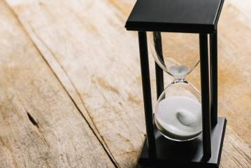Sand running through the bulbs of an hourglass measuring the passing time in a countdown to a deadline, on a wooden background with copy space- Stock Photo or Stock Video of rcfotostock | RC-Photo-Stock