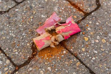 Scattered pieces of a firecracker are spread on the ground. : Stock Photo or Stock Video Download rcfotostock photos, images and assets rcfotostock | RC-Photo-Stock.: