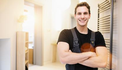 smiling handsome plumber standing with crossed arms and looking at camera in bathroom Room- Stock Photo or Stock Video of rcfotostock | RC-Photo-Stock
