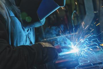 strong man is a welder, in a welding mask and welders leathers, a metal product is welded with a welding machine in the garage, blue sparks fly to the sides - Stock Photo or Stock Video of rcfotostock | RC-Photo-Stock