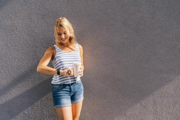 Stylish happy young woman looking to her clock. She holds paper coffee to go and enjoying the sunlight in the city. portrait of smiling girl , lifestyle concept image.- Stock Photo or Stock Video of rcfotostock | RC-Photo-Stock