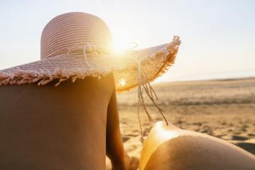 tanning woman wearing sun hat over her legs on the beach at sunset- Stock Photo or Stock Video of rcfotostock | RC-Photo-Stock