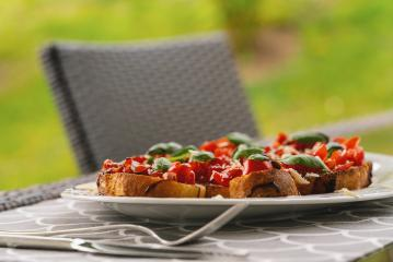 Tasty savory tomato Italian appetizers, or bruschetta, on slices of toasted baguette garnished with basil, close up on a Plate on a table outside- Stock Photo or Stock Video of rcfotostock | RC-Photo-Stock