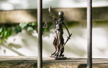 The Statue of Justice - lady justice or Iustitia / Justitia the Roman goddess of Justice against a jail grid- Stock Photo or Stock Video of rcfotostock | RC-Photo-Stock