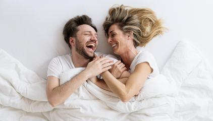 Top view of young loving couple lying on bed laughing and smiling with blanket. They are looking at each other with trust in love- Stock Photo or Stock Video of rcfotostock | RC-Photo-Stock