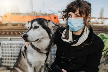 Travel with dog during pandemic. Casual Woman is waiting for the train with her dog on the platform and is wearing a face mask because of the coronavirus. Lovely  und happy friendship with your pet : Stock Photo or Stock Video Download rcfotostock photos, images and assets rcfotostock | RC-Photo-Stock.: