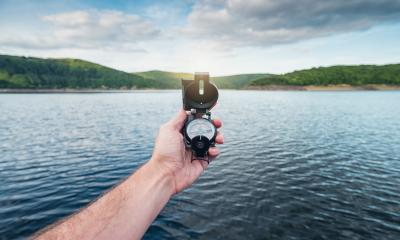 Traveler man searching direction with a compass on a coastline near a lake in the mountains. Point of view shot.- Stock Photo or Stock Video of rcfotostock | RC-Photo-Stock