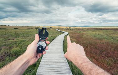 Traveler young man searching direction with a compass in the landscape with Wooden boardwalk . Point of view shot- Stock Photo or Stock Video of rcfotostock | RC-Photo-Stock