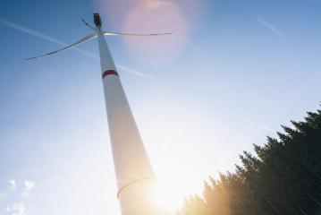 Wind turbine in the forest against sunlight- Stock Photo or Stock Video of rcfotostock | RC-Photo-Stock