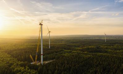 Wind turbines under construction in the forest - Energy Production with clean and Renewable Energy - aerial shot- Stock Photo or Stock Video of rcfotostock | RC-Photo-Stock