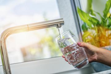 Woman filling a glass of water from a stainless steel or chrome tap or faucet, close up on her hand and the glass with running water and air bubbles- Stock Photo or Stock Video of rcfotostock | RC-Photo-Stock