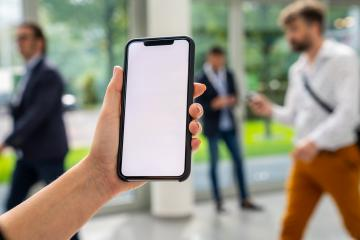 Woman hand holding black cellphone with white screen at a trade fair, copyspace for your individual text.- Stock Photo or Stock Video of rcfotostock | RC-Photo-Stock