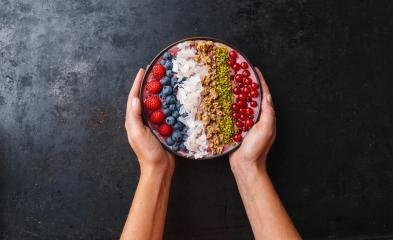 Woman hands hold a Healthy breakfast bowl, wirh blueberry smoothie with, raspberry, blueberrys, coconut, nuts and currants toppings- Stock Photo or Stock Video of rcfotostock | RC-Photo-Stock