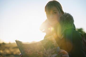 Woman hiker with a backpack and a map , searching right direction in the wilderness at sunset : Stock Photo or Stock Video Download rcfotostock photos, images and assets rcfotostock | RC-Photo-Stock.: