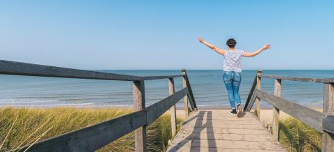 woman is raising hands on a wooden path to the Baltic sea over sand dunes- Stock Photo or Stock Video of rcfotostock | RC-Photo-Stock