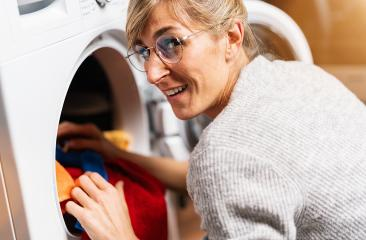 Woman putting clothes out washing machine or dryer, home laundry service : Stock Photo or Stock Video Download rcfotostock photos, images and assets rcfotostock | RC-Photo-Stock.:
